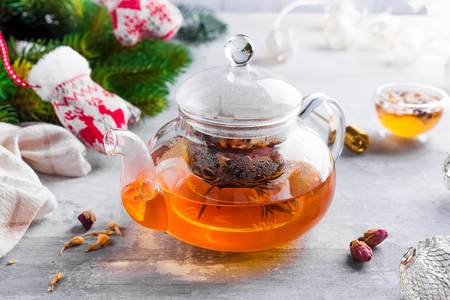 Glass teapot with flowers tied tea, Hot tea in glass teapot and honey with metal honey stick on stone