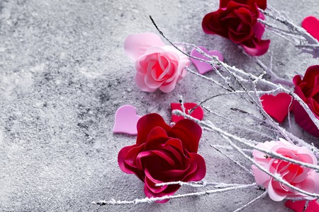 Branches in the snow with pink and red rose buds and hearts on a concrete background with space for text. Valentines day concept