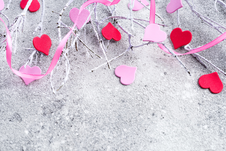 Branches in the snow with pink and red hearts on a concrete background with space for text. Valentines day concept