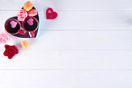 two cups of coffee, macaroons with flowers in a box in the form of a heart on a white background. Valentines day concept, flat lay with copy space Banco de Imagens
