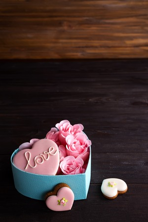 Hearts cookies in box. Festive round blue box with cookies and Rose on dark wooden background, copy space