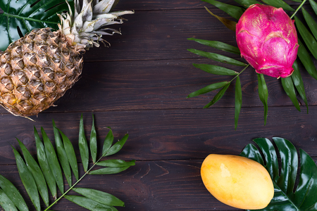 Tropical fruit frame with pineapple, dragon fruit, yellow mango and palm leaves on a dark wooden
