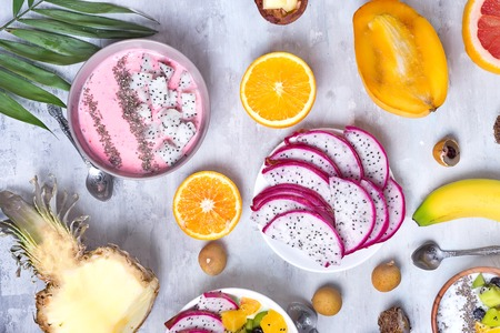 Breakfast table with yogurt strawberry smoothie bowls and fresh tropic fruits on a gray stone