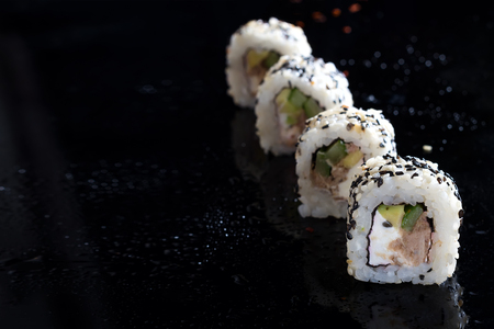 Sushi roll with fish, vegetables and cheese on black glass with reflection. Traditional japanese food copy space Reklamní fotografie