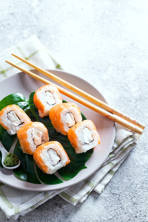 Philadelphia roll classic on a plate with chopsticks. Japanese sushi food. Copy space Stock Photo - 124310839