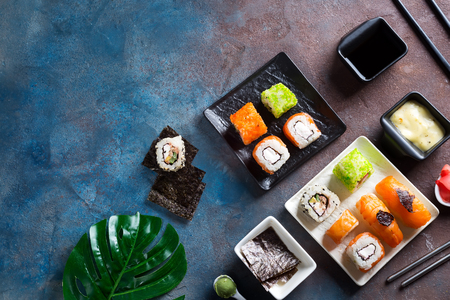 Set of maki roll and green leaves palm on stone table. Copy space