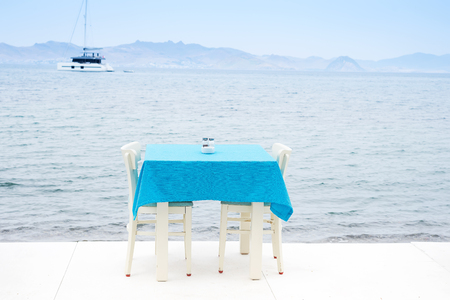 Cafe table served with a blue tablecloth near the sea coast for relaxing holidays vacations