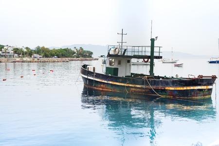 Old rusty fishing boat on the Aegean Sea, moored to the shore, Turgutreis Turkey Stock Photo