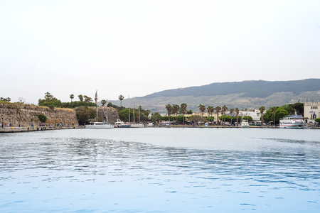 The scenic port with traditional views of the city, palm trees and boats in the village , Kos island, Greece