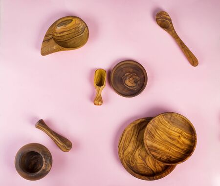 Set of wooden kitchen utensils made from olive wood on pink background, flat lay