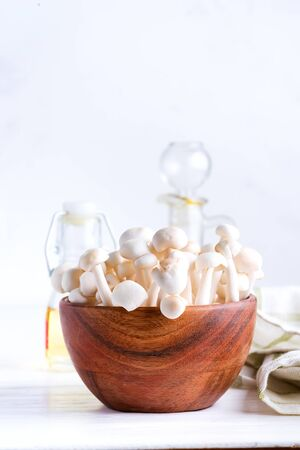 White buna-shimeji in wooden rustic bowl on white background
