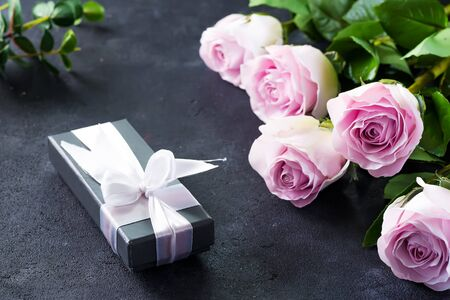 Pink roses and a gift box on a stone background. Vintage style, retro interior with flowers. Space for text 写真素材