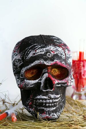 Skull with syringes with tomato juice in the hay as a decoration for Halloween party at home