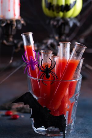 Bloody cocktail in glass tubes for Halloween party celebration. Black stone background Stok Fotoğraf