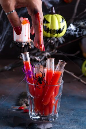 Bloody cocktail in glass tubes for Halloween party celebration with bloody finger. Black stone background Stok Fotoğraf