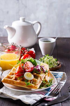 Gaufres belges à l'avocat, œufs, micro vert et tomates avec jus d'orange et thé sur table en bois. Petit déjeuner parfait pour une alimentation saine ou perdre du poids. Sandwich à l'avocat.