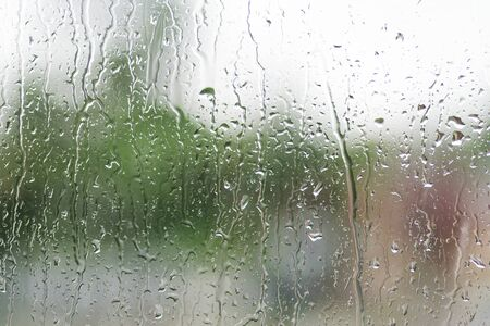 Rain drops on the window with green over background