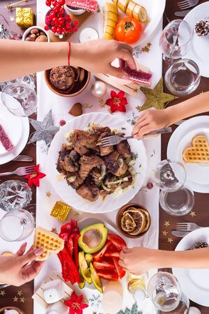 Christmas table setting with food on a plate, mom and child hands handing food and decoration on dark wooden table, flat lay