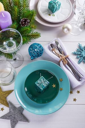 Place table setting for Christmas white table with purple decor elements with green branches Christmas tree Stock Photo