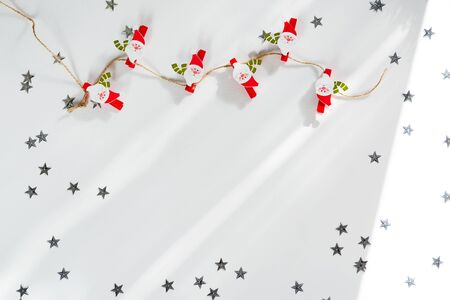 Christmas decorations Santa Claus clothespins on the white background. Christmas frame
