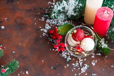 Red and white Christmas ball in a glass jar, color candles, fir branches and berries on a dark stone background with copy space