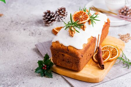 Fruit cake dusted with icing, nuts and dry orange on stone background. Christmas and Winter Holidays homemade cake