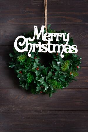 Christmas decoration wreath of green leaves and berries holly ilex plant with letter Merry Christmas on dark wooden background