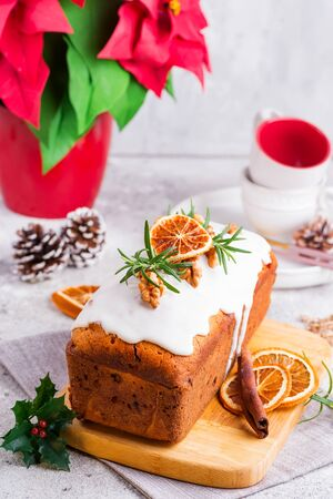 Fruit loaf cake dusted with icing, nuts and dry orange on stone background. Christmas and Winter Holidays homemade cake