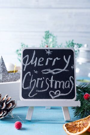 Black chalkboard with caption Merry Christmas! and christmas decoration on blue