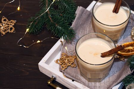 Homemade White Holiday Eggnog with a Cinnamon Stick on dark
