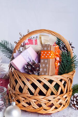 Christmas composition with box, basket, pine cones and decorations on white wooden with copy space