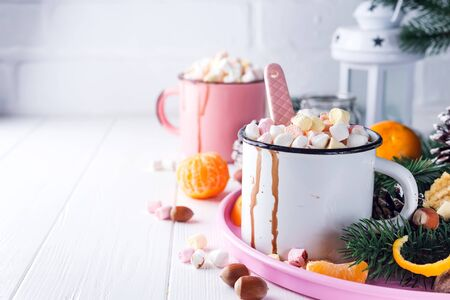 Cups of hot chocolate with marshmallows, mandarin, fir tree branches and nuts on white wooden