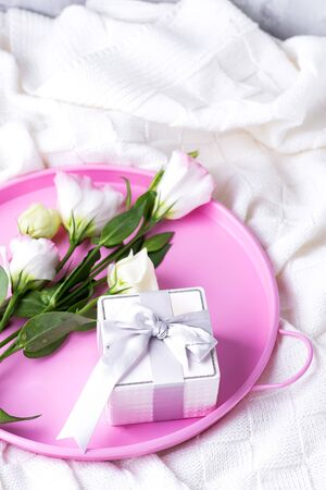 Gift box and pastel flowers eustoma for Valentines or Mothers day on pink tray on bed