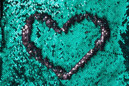 Heart sign frame on a sequins green glitter  texture, copy space