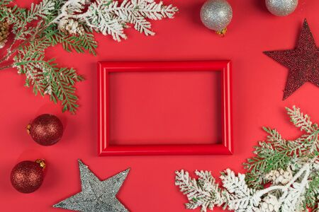 Red photo frame with branches in the snow, christmas toys on red