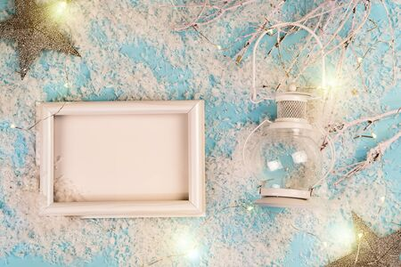 White christmas lantern with white photo frame in the snow and blue  with stars Reklamní fotografie