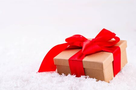 Decorative brown gift box with a large red bow standing in fresh snow Reklamní fotografie
