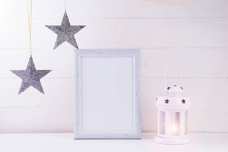 Photo mock up with white frame, stars and lantern on white wooden background, copy space. Christmas concept