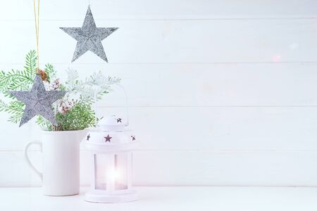 Photo mock up with pine branches in vase, stars and lantern on white wooden background, copy space. Christmas concept