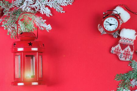 Christmas greeting card with red lantern, red clock, snow branches and mittens on red background. View from above