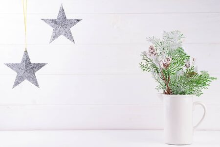 Copy space with pine branches in vase, stars on white wooden background, copy space. Christmas concept Reklamní fotografie