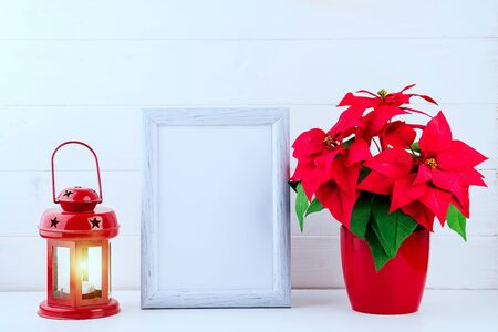 Photo mock up with white frame, Poinsettia in a flowerpot and red lantern on white wooden background, copy space. Christmas concept