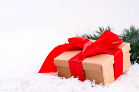 Decorative brown gift box with a large red bow standing in fresh snow against a background