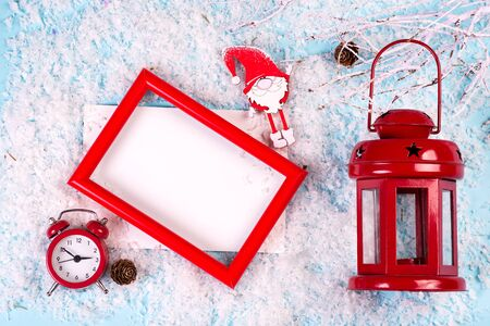 Photo mock up with red frame, clock and lantern on white snow background, copy space. Christmas concept Reklamní fotografie