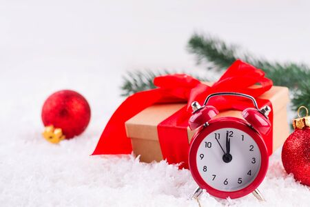 Red old clock with red balls, brown gift box with a large red bow standing in fresh snow against a background. Christmas time