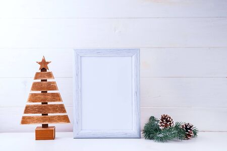 Photo mock up with white frame, wooden tree and pine branches on white wooden background, copy space. Christmas concept Reklamní fotografie