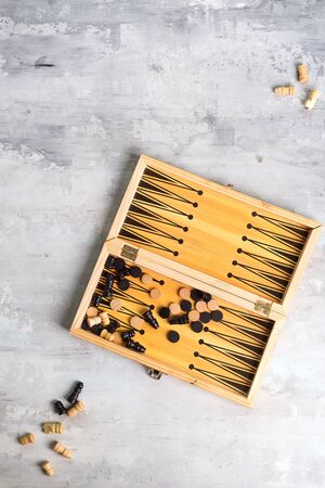 backgammon dice and pieces with a pair of chess pieces on the stone background, flat lay
