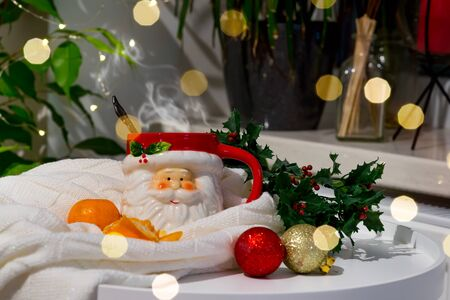 A cup in the form of Santa with hot tea and tangerines in a plaid with highlights on a background of greenery Stock Photo