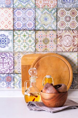 wooden bowls and olive oil on a stone countertop on a background of old colored tiles, facade kitchen interior Stock Photo