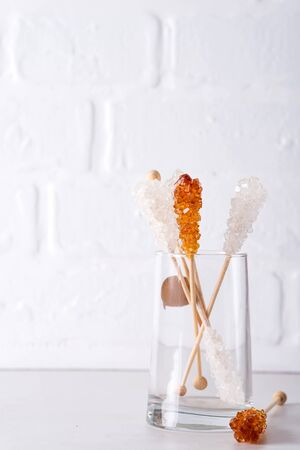 Candy brown and white sugar on a sticks in glass on white background.
